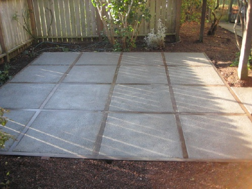 Decorative concrete pad with wood dividers
